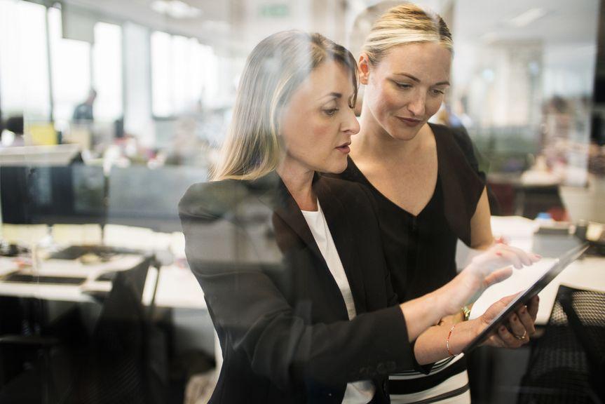 Zwei Frauen arbeiten gemeinsam im Grossraumbüro