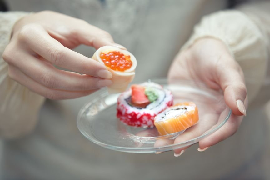 Frauenhände mit einem Teller Sushi
