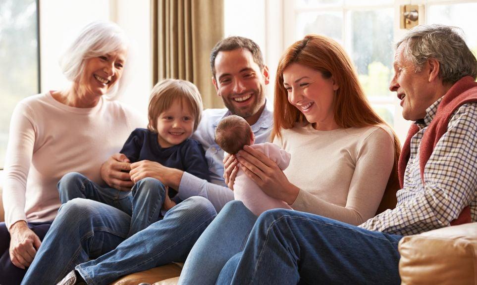 Familie, mit Neugeborenem, sitzt mit den Grosseltern auf dem Sofa