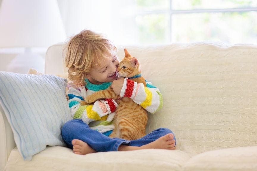 Kind mit Katze auf dem Sofa
