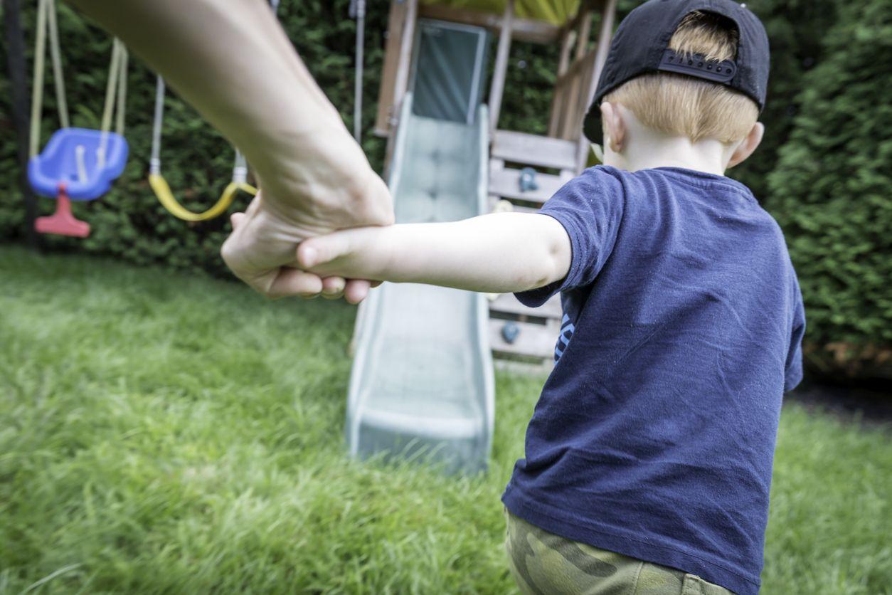 Kind rennt mit Erwachsenem auf den Spielplatz