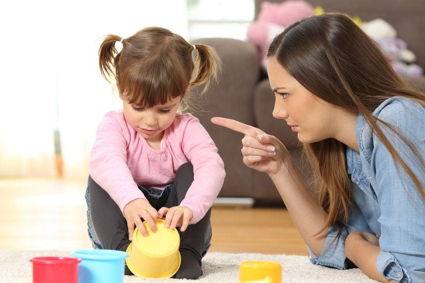 Mutter zeigt tadelnd mit dem Finger auf ihre Tochter