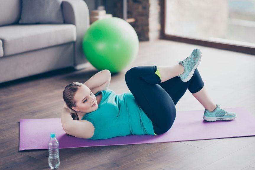 Frau zu Hause auf einer Yogamatte macht Beckenboden- und Bauchmuskelübungen