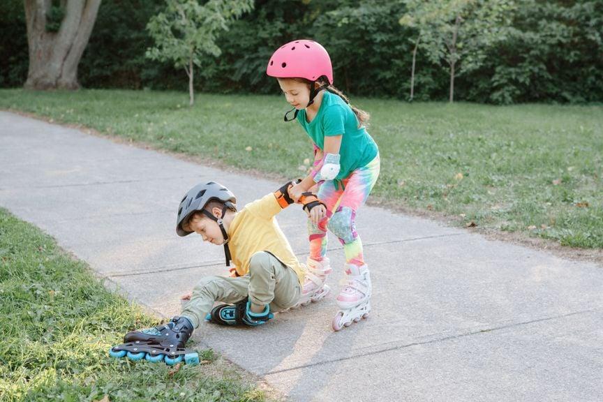 Mädchen hilft gestürztem Roller Blader