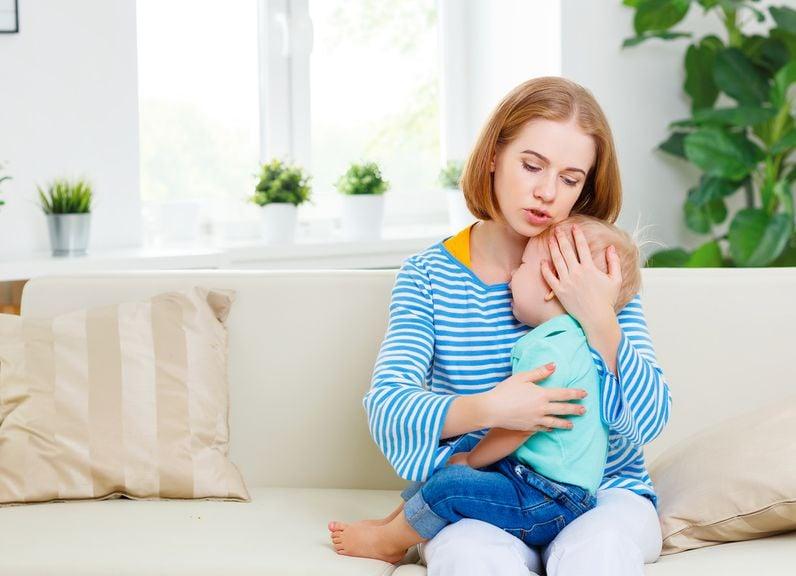 Mutter tröstet Kind auf dem Sofa
