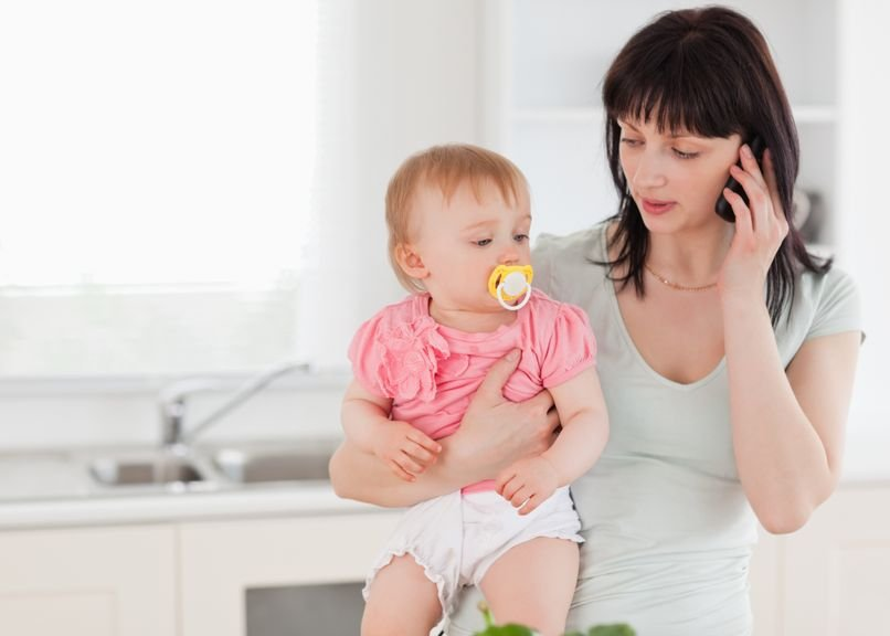 Mutter mit Baby im Arm telefoniert