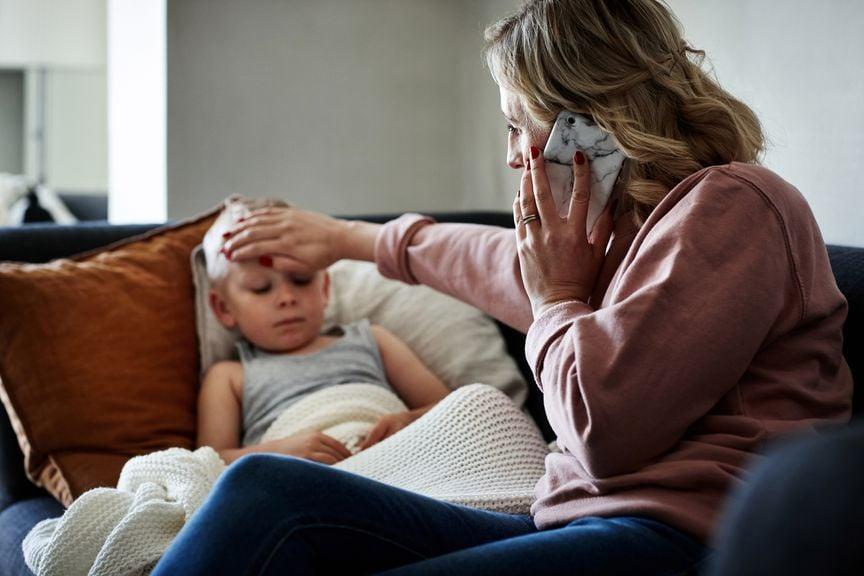 Mutter mit fieberndem Kind am Telefon