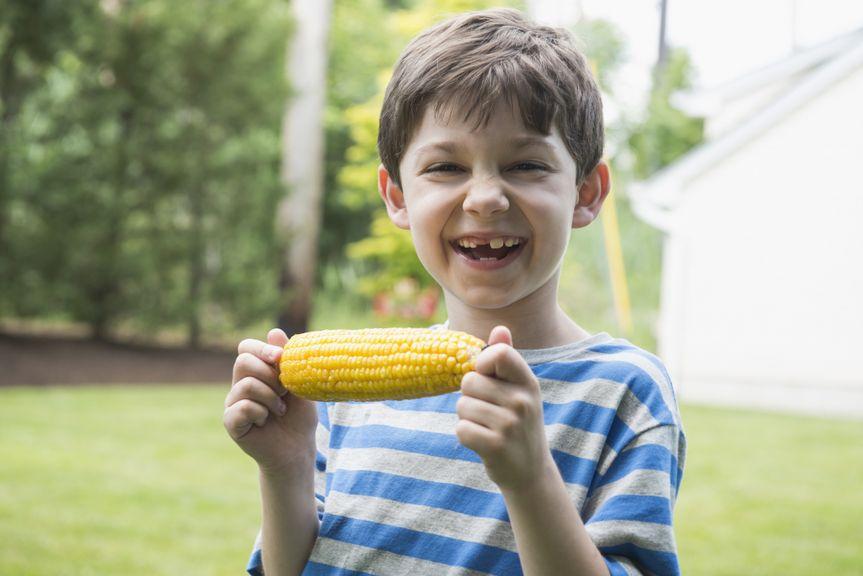 Junge mit Zahnlücken und Maiskolben