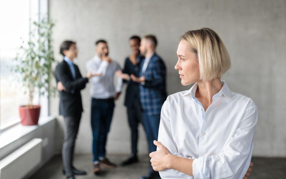 Männer sprechen sich bei der Arbeit hinter dem Rücken einer Frau ab