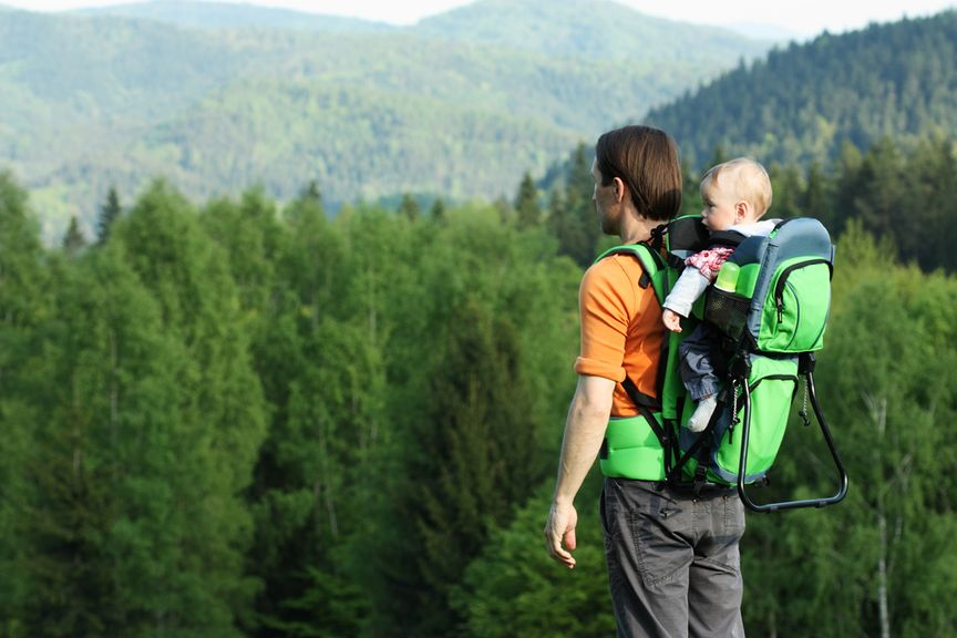 Vater in den Bergen mit Baby in der Rückentrage