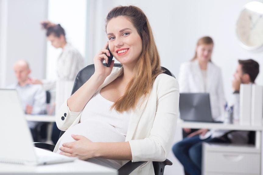 Schwangere sitzt am Schreibtisch und telefoniert