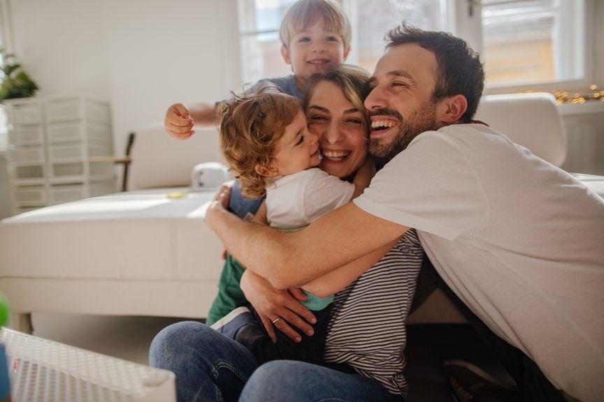 Vierköpfige Familie umarmt sich lachend