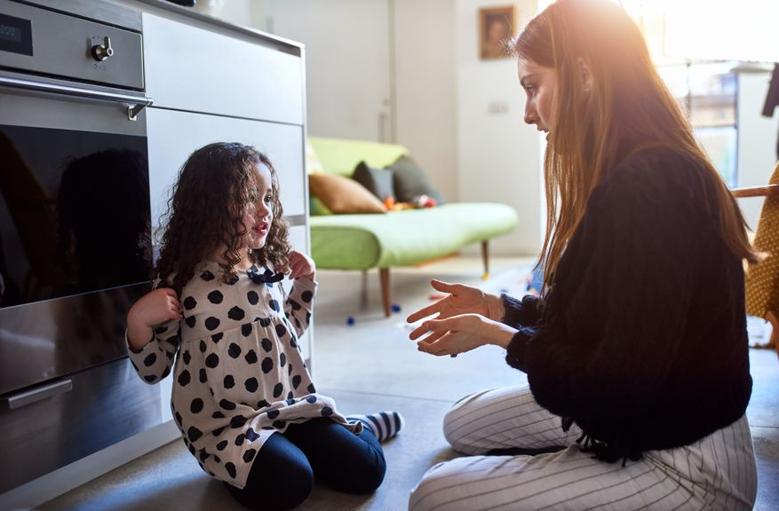 Mutter diskutiert mit Tochter auf dem Fussboden