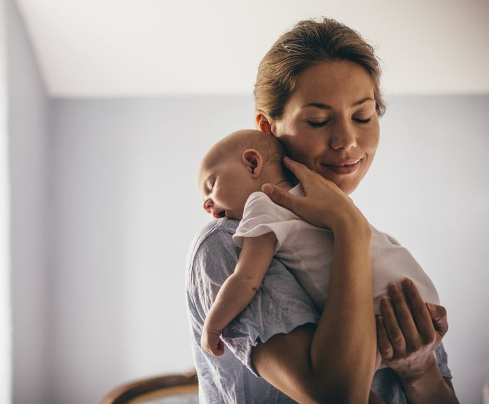 Mutter mit schlafendem Säugling an der Schulter
