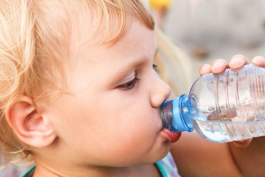 Kleiner Junge trinkt Wasser aus der Flasche