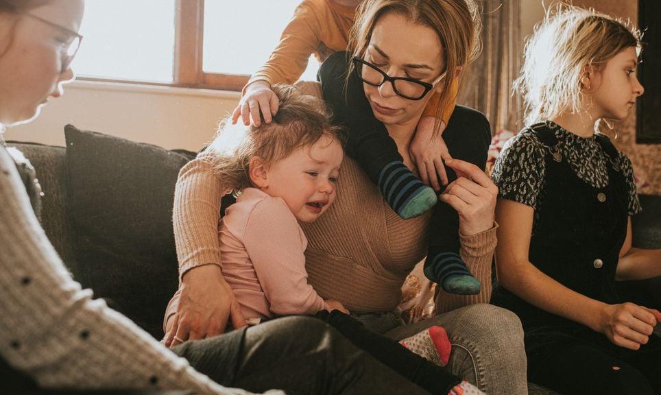Mutter mit vier Kindern tröstet Mädchen