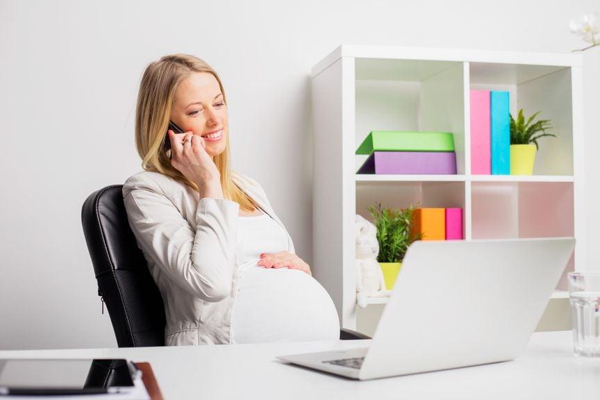 Schwangere am Schreibtisch mit Laptop und Telefon