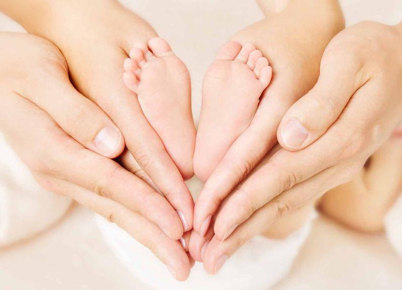 Hände von Mutter und Vater umfassen die Füsse des Neugeborenen
