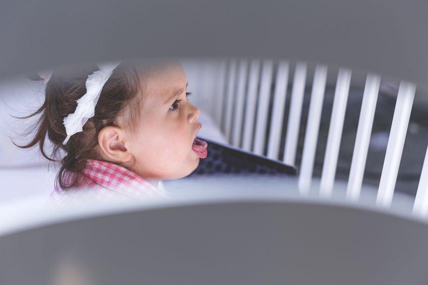 Kind im Gitterbett