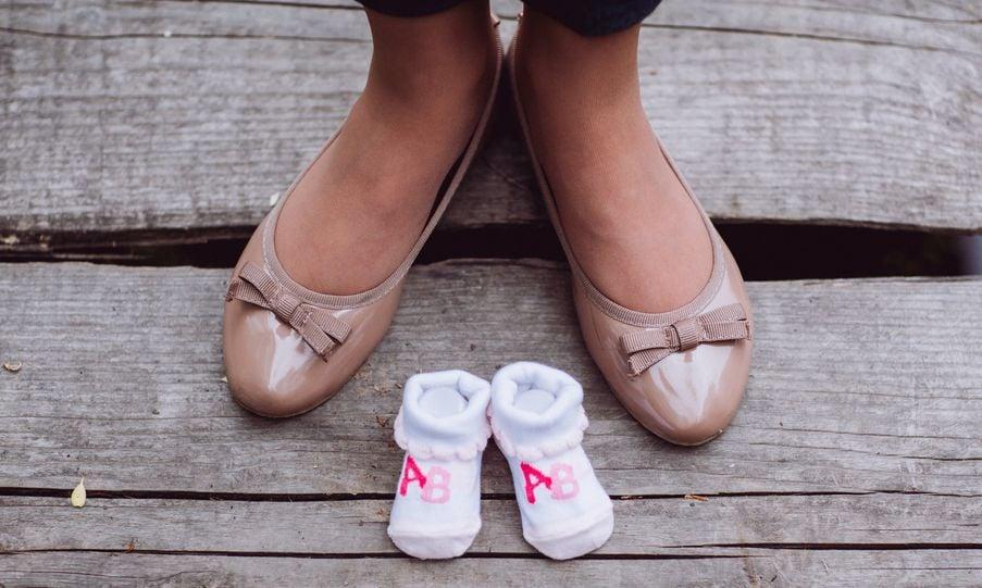 Füsse in Ballerinas, dazwischen Babysöckchen