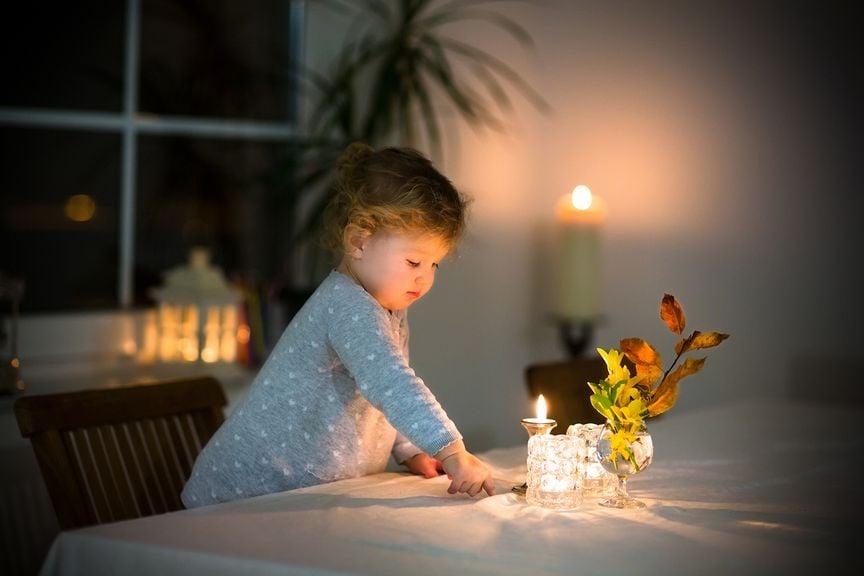 Kind vor einer brennenden Kerze