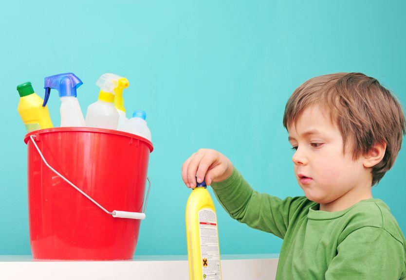 Kind spielt mit Putzmitteln