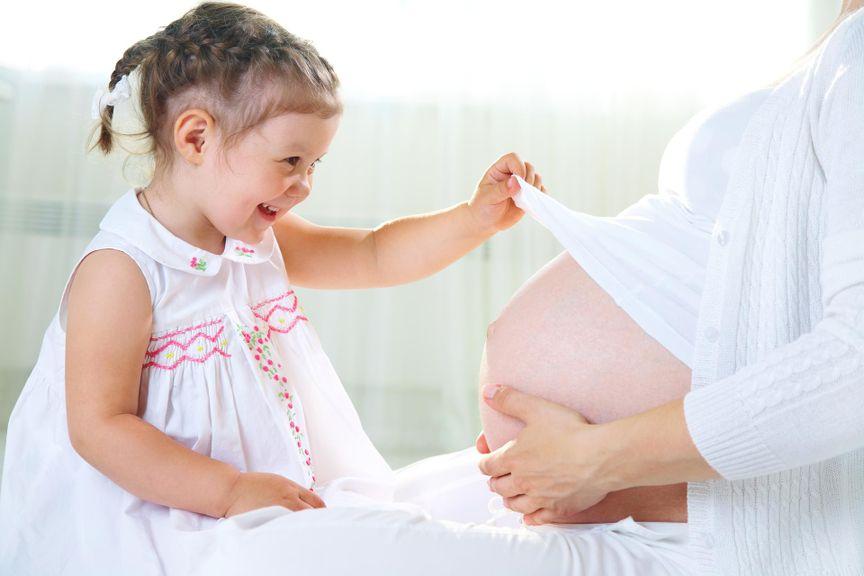 Mädchen hebt der Mutter das T-Shirt und stahlt den Babybauch an
