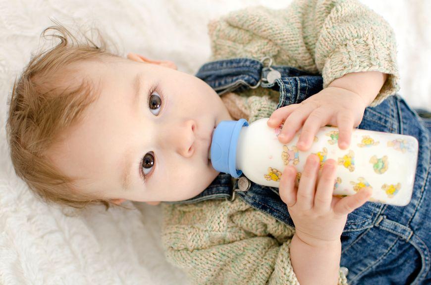 Baby im liegen, trinkt aus der Schoppenflasche
