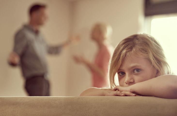Trauriges Kind, Eltern streiten im Hintergrund