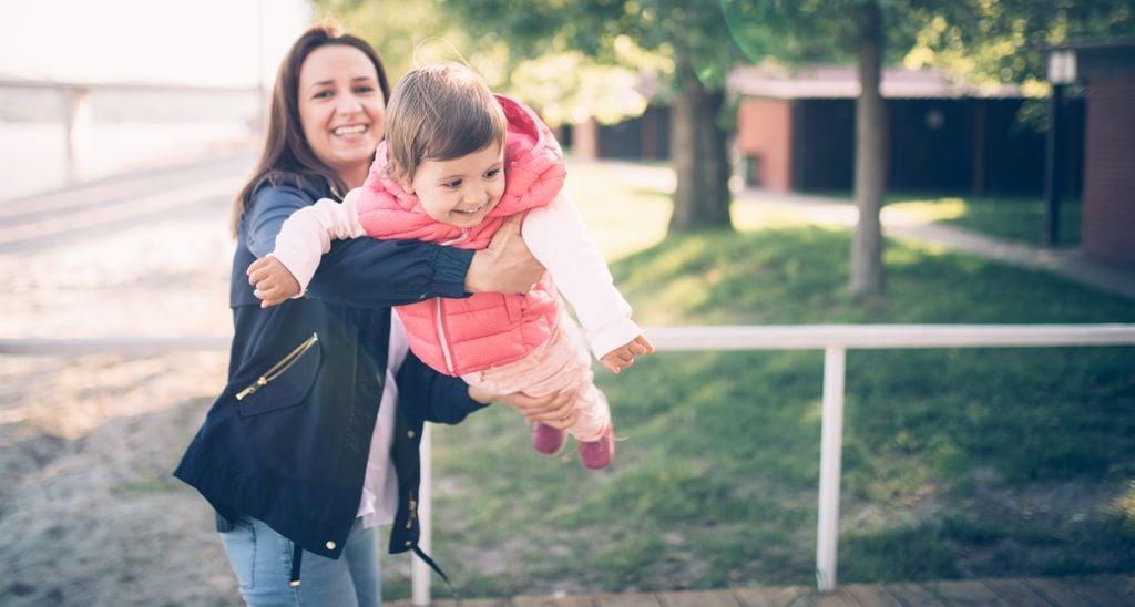 Frau mit Kind auf dem Spielplatz
