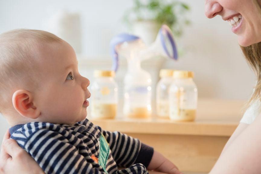 Baby schaut aufmerksam die Mutter an, im Hintergrund abgepumpte Muttermilch in Flaschen