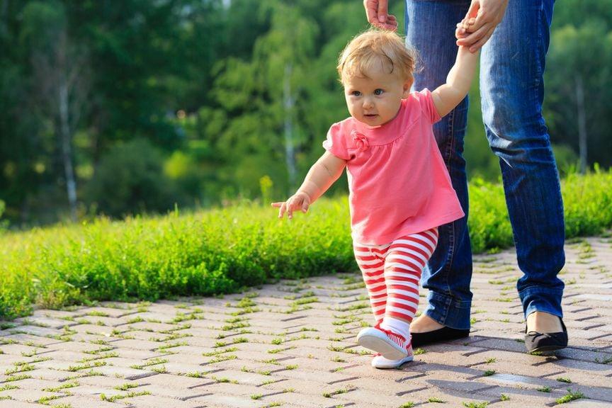 Baby läuft mit Hilfe der Mutter