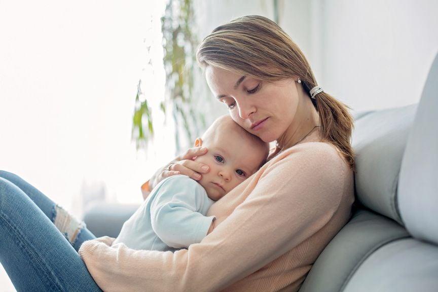 Mutter hält ihr krankes Baby im Arm