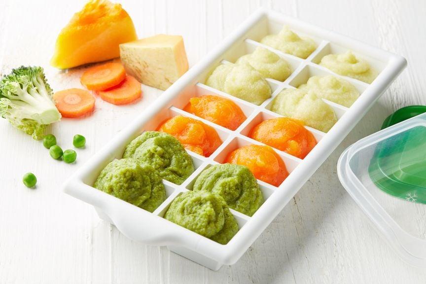 Gemüsestücke und püriertes Gemüse in Eiswürfelbehälter zum Einfrieren