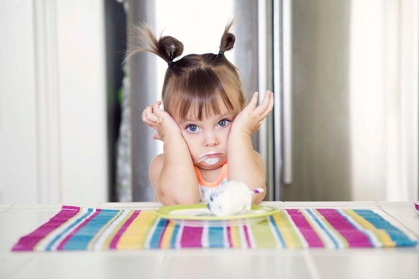Mädchen sitzt unglücklich vor einer Schale mit Quark oder Joghurt