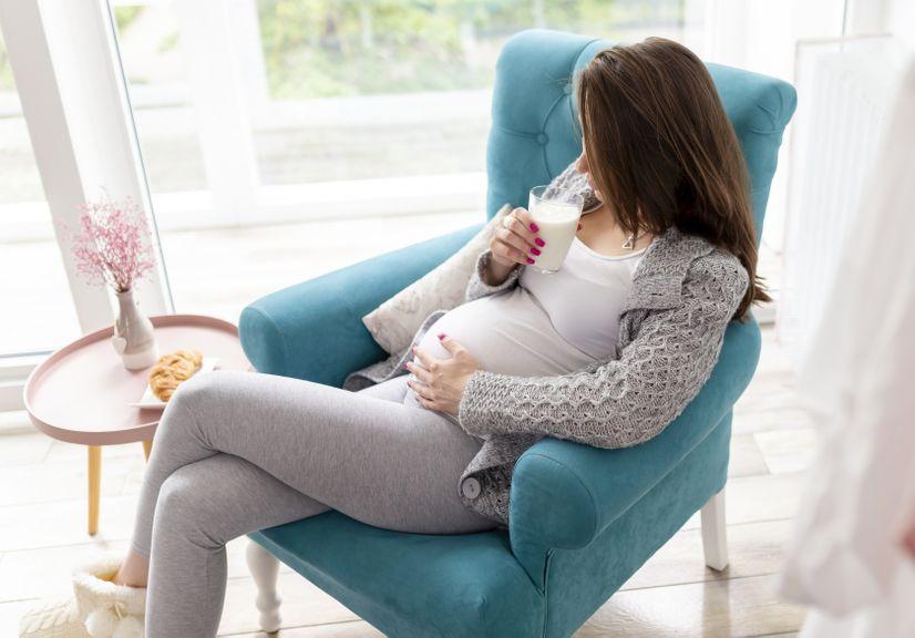 Schwangere im Sessel trinkt Milch