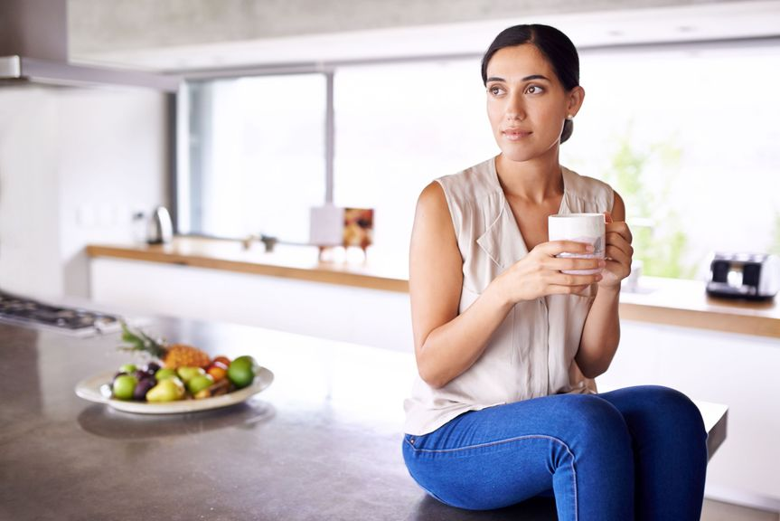 Frau sitzt auf der Kochinsel mit einer Tasse in der Hand