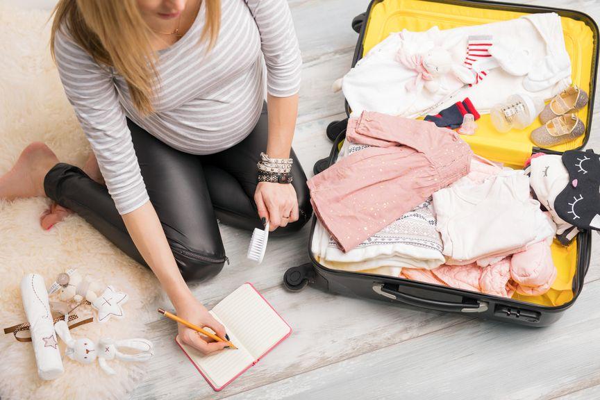 Schwangere packt den Koffer fürs Spital mit der Checkliste