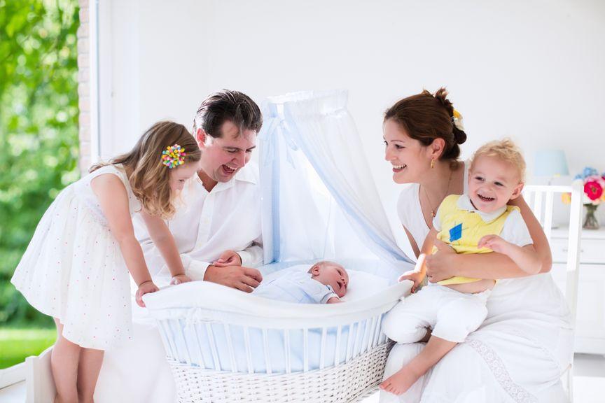 Eltern, Kinder und Neugeborenes in der Wiege