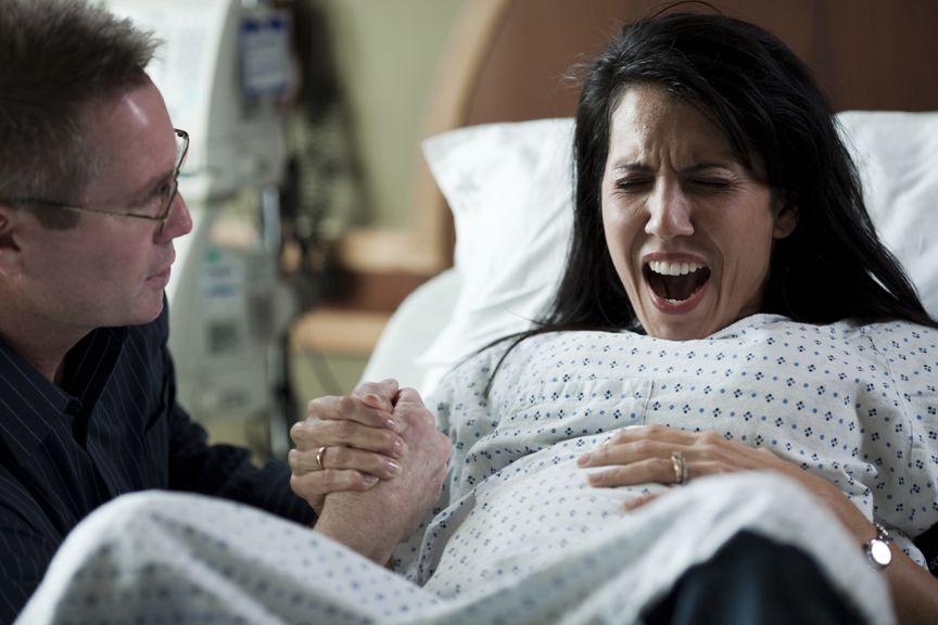 Gebärende schreit während der Wehe, Partner hält ihre Hand
