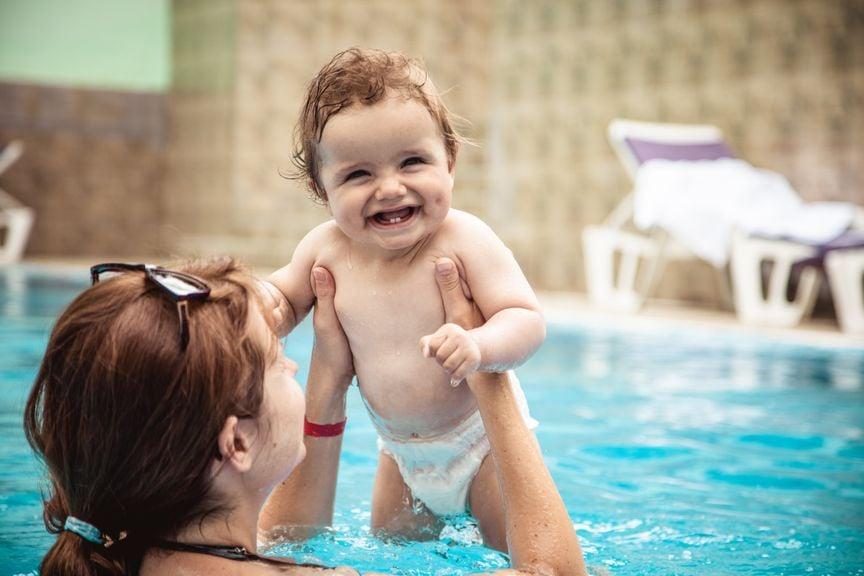 Lachendes Baby mit Mutter im Wasser