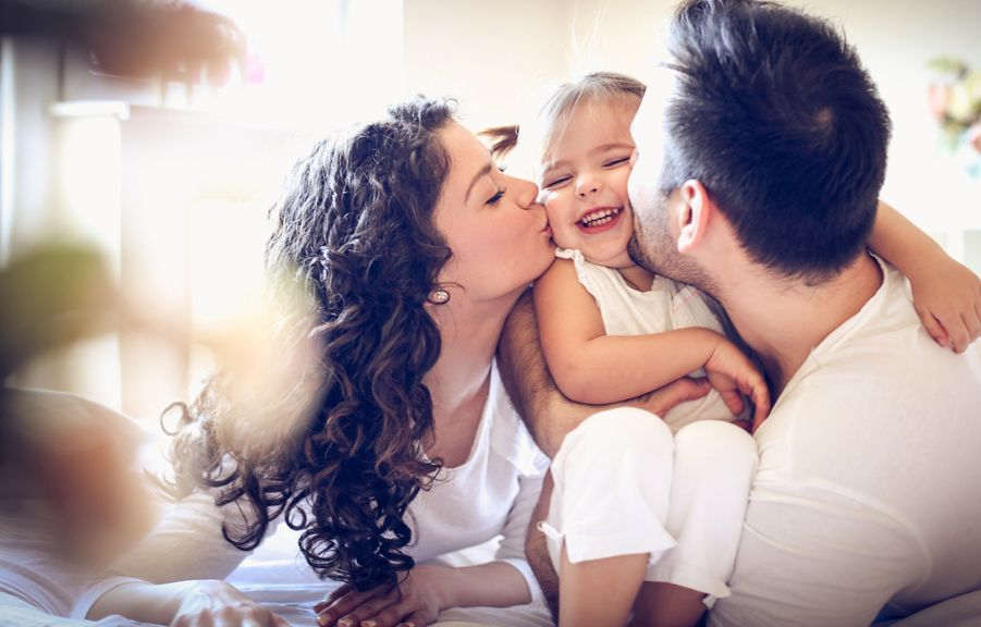 Eltern küssen und umarmen ihr Kind
