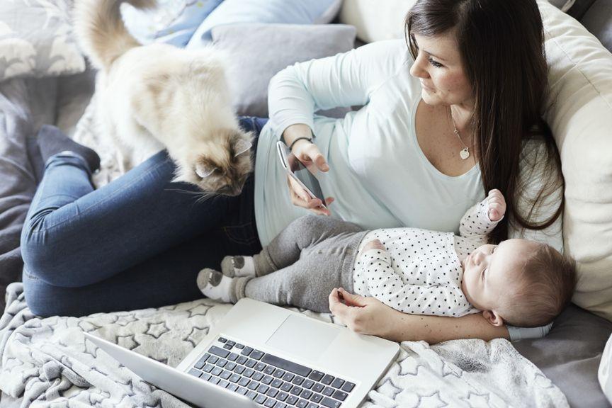 Mutter liegt mit Baby und Katze auf dem Sofa