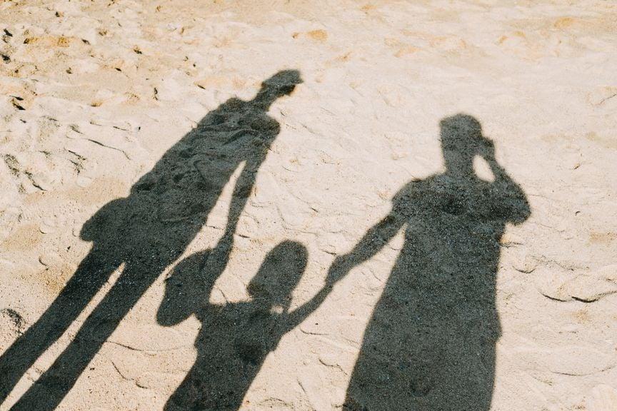 Schatten von Elternpaar mit Kind am Strand