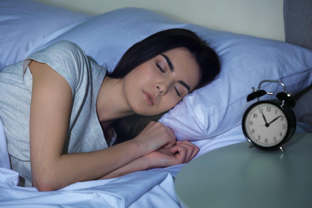Frau schläft im Bett, Wecker auf dem Nachttisch
