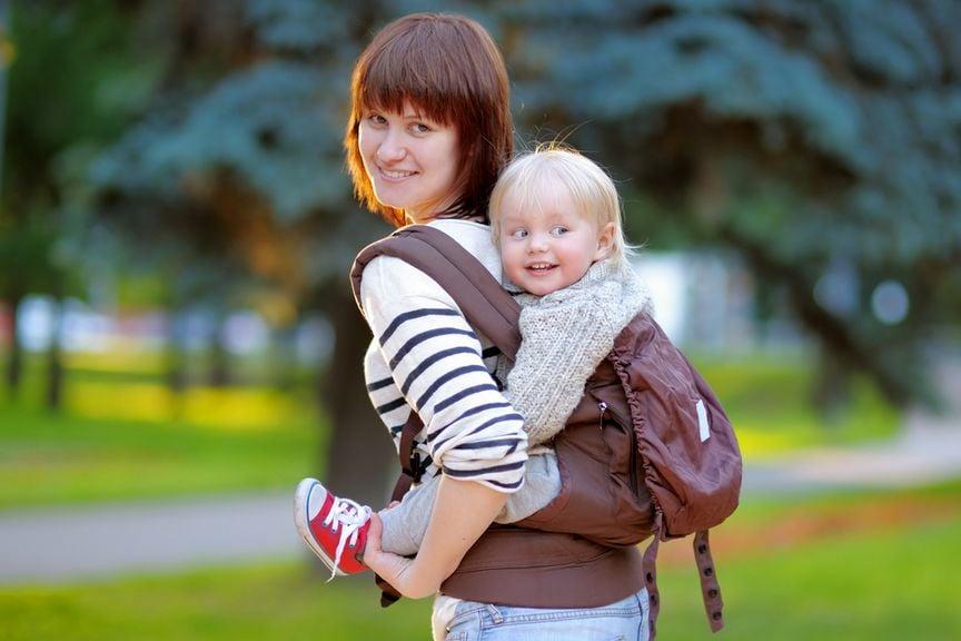Mutter mit Baby unterwegs in der Rückentrage
