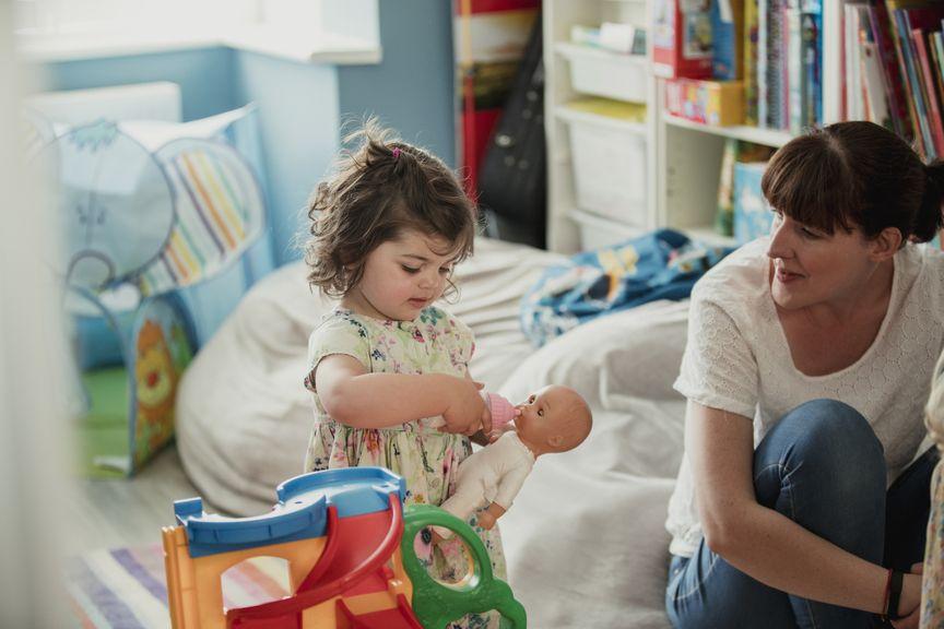 Kind mit Mutter beim Puppenspiel