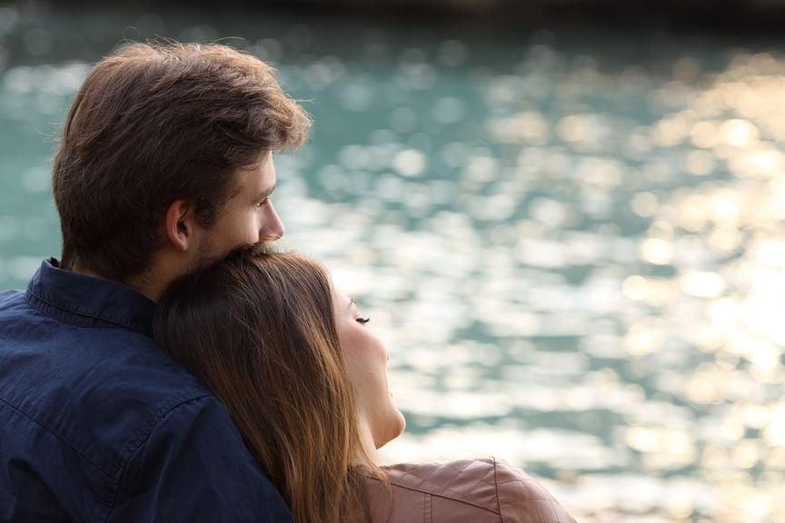 Paar sitzend am Wasser, sie lehnt sich an ihn