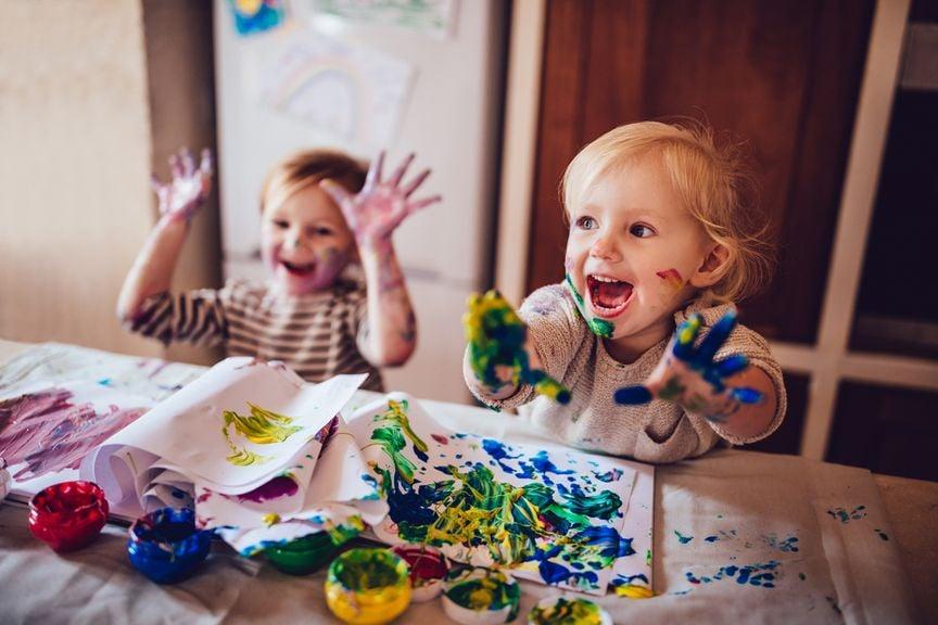 Zwei Kinder haben viel Spass mit Fingerfarben