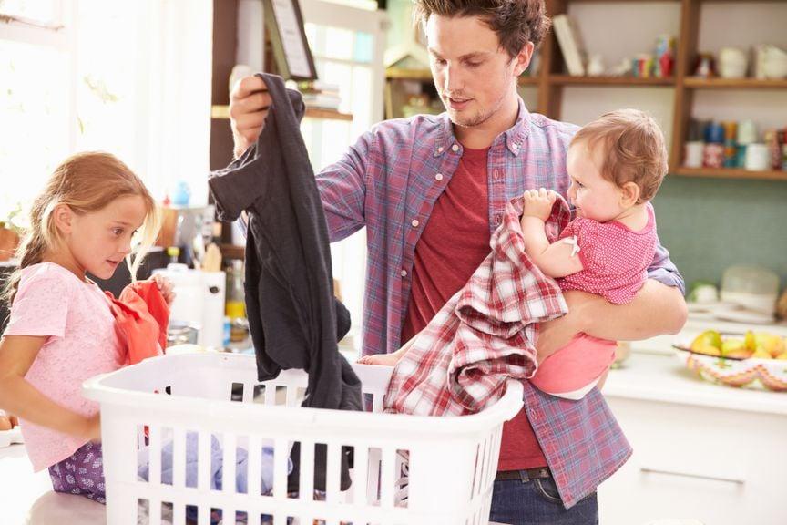 Vater mit zwei Kindern beim Wäsche sortieren
